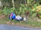 Assorted rubbish, nappies, building material flytipped by side of road